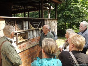 Eine Besuchergruppe im Freilandlabor begutachtet ein Insektenhotel